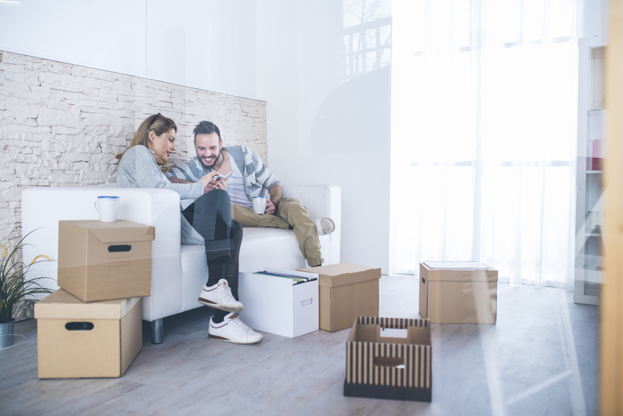Man and woman looking at smartphone while packing boxes